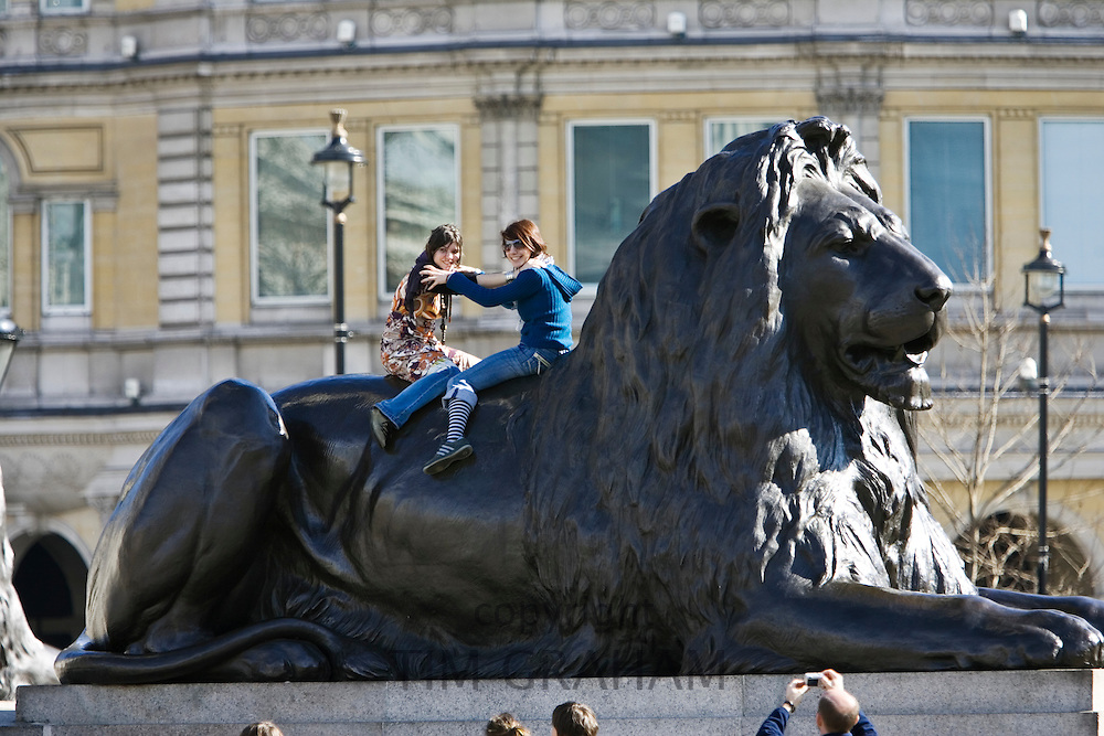 Tourists pose for photographs on lion statues in Trafalgar Square, London, UK