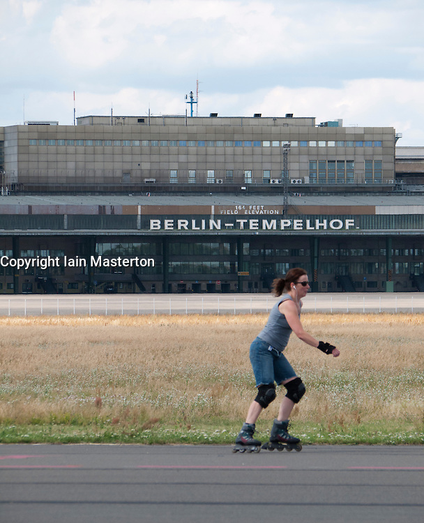 Woman inline skating along runway at new city public Tempelhofer Park on site of famous former Tempelhof Airport in Berlin Germany