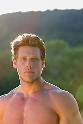 portrait of a good looking All American man without a shirt at sunset