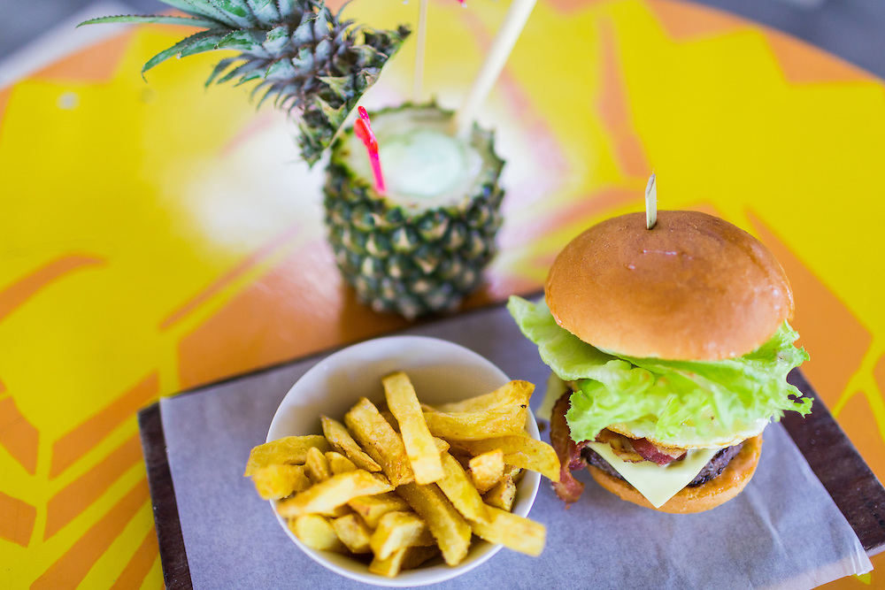 Burger 'The Lot' - Wagyu beef patty, bacon, egg, pineapple, cheese, onion, tomato, pickle, lettuce, mayo on home baked, toasted brioche bun & Old Man's hand cut chips with Coco-Colada Pinada colada bionically enhanced with coconut pandan gelato.