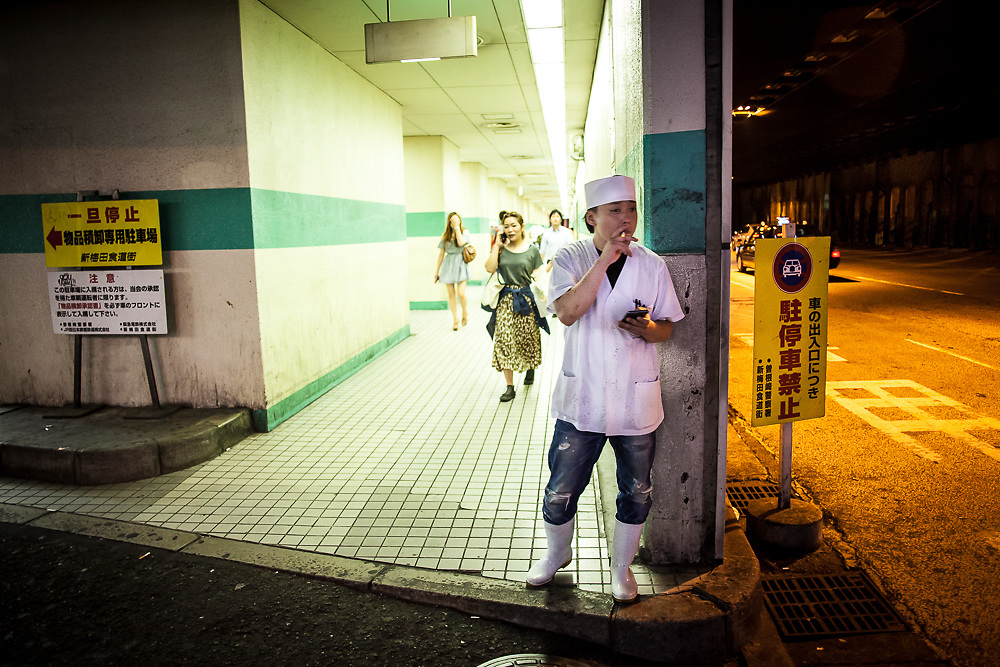 A chef finds a quiet spot for a break in the Friday evening bedlam of downtown Osaka