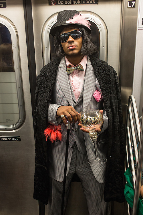 New York, NY, October 31, 2013. A man in a striped suit, carrying a cane and a huge goblet rides the F train home from New York's Greenwich Village Halloween Parade.