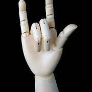 A wooden artists modelling hand showing the surfing gesture for shaka - right on
