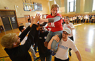 "Up2Us Coach Across America coaches Ski Bailey (R) and Dr. Ajamu Banjoko (C) carry Up2Us Center Vice President Megan Bartlett on their shoulders as Laureus USA and Mercedes-Benz USA celebrate ""Healthy Futures""-Up2Us' National Coach Training Institute at Wells Senior High School on March 4, 2014 in Chicago, Illinois.  (Getty Images for Laureus)"