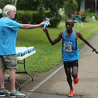 The lead runner grabs a water at the water station set up on Clayton Ave during the Gumtree Run Saturday morning in Tupelo.