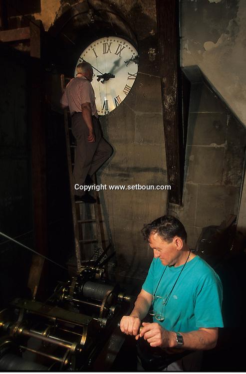 France. Paris. Man Adjusting Clock at Palais de Justice in  City hall  13th ardt