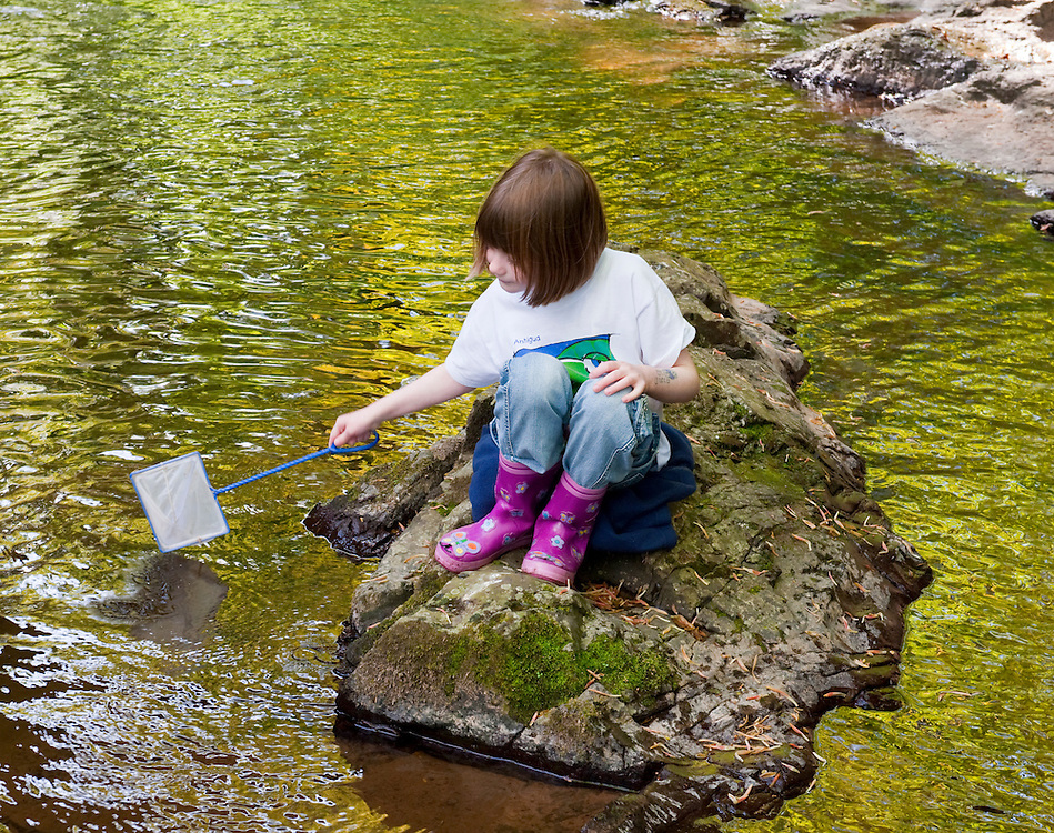 Girl playing beside a small river, Angus, Scotland