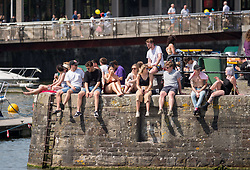 © Licensed to London News Pictures. 29/06/2019. Bristol, UK. Hot weather at Bristol Docks and Harbourside on the hottest day of the year across the UK. People sit on the harbour walls and go out in boats and use paddle boards. Photo credit: Simon Chapman/LNP.