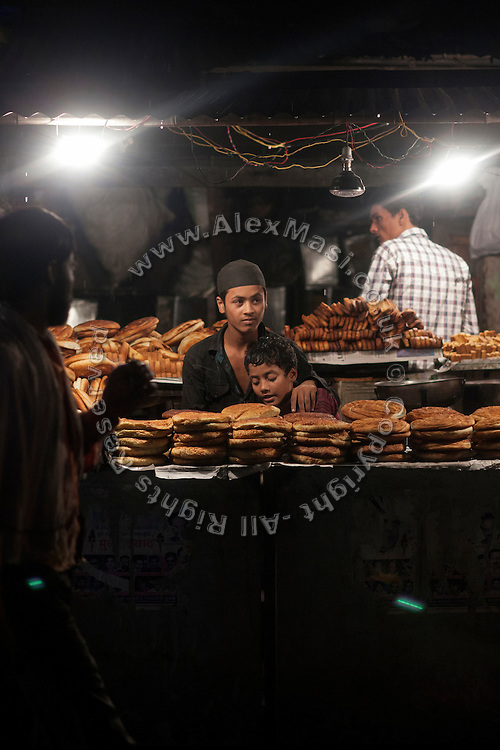 During the holy month of Ramadan, two Muslim brothers selling bread and sweets are embracing inside their stall in Kasi Camp, one of the nineteen water-affected colonies surrounding the abandoned Union Carbide (now DOW Chemical) industrial complex in Bhopal, Madhya Pradesh, India.