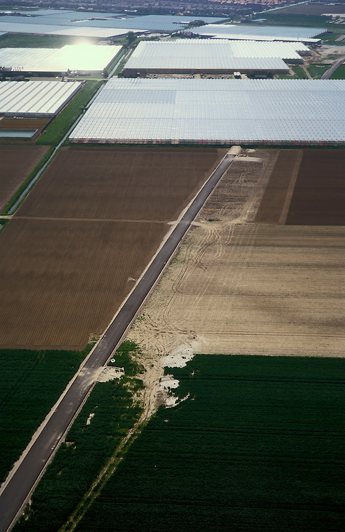 Nederland, Bleiswijk, Oosteindsche Polder, 17/05/2002; de HSL doorsnijdt het glastuinbouwgebied en grote kassen complexen moeten worden gesloopt; de werkweg voor de HSL (diagonaal) is in aanleg: tijdelijke akkers waar eerst kassen stonden, ook de kassen rechts bovne het midden zullen er aan moeten geloven; verkeer en vervoer, infrastructuur, bouwen, spoor, rail, TGV planologie ruimtelijke ordening, landschap.<br /> luchtfoto (toeslag), aerial photo (additional fee)<br /> foto /photo Siebe Swart