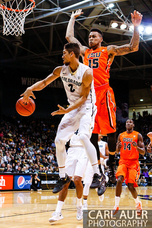 January 2nd, 2014:  Colorado Buffaloes junior guard Askia Booker (0) dishes the ball past Oregon State Beavers junior forward Eric Moreland (15) in the first half of action in the NCAA Basketball game between the Oregon State Beavers and the University of Colorado Buffaloes at the Coors Events Center in Boulder, Colorado