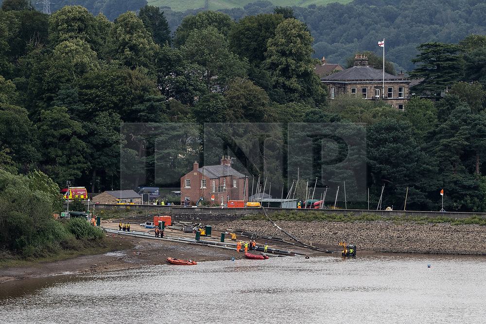 © Licensed to London News Pictures. 04/08/2019. Whaley Bridge, UK. Heavier pumping equipment is deployed to accelerate draining the reservoir . More rain is forecast overnight (Sunday 4th/Monday 5th August) in the town of Whaley Bridge in Derbyshire after earlier heavy rain caused damage to the Toddbrook Reservoir , threatening homes and businesses with flooding. Photo credit: Joel Goodman/LNP