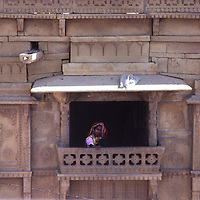 """A Rajasthani woman sits at a balcony window in the """"golden city"""" of Jaisalmer in Rajasthan."""