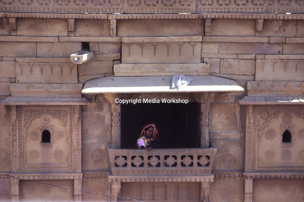 "A Rajasthani woman sits at a balcony window in the ""golden city"" of Jaisalmer in Rajasthan."
