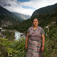 October 2009 WWF Everest - Village of Ghat with Dudh Koshi river and valley in back with Ang Kandu Sherpa - pictured with river in background what she saw during the Glof in 1985 -  The water was rolling down the valley massive flood rolling down  - all the cattle and livestock were stranded on the other side of the river ..Black water came rolling down and cut the banks into the farmland and caused the damage. She and all people who live along the bank of the river are worried and concerned about a possibility of a new GLOF - they are always on alert especially during the monsoon season.  She is aware of Climate Change and thinks the erratic rainfall and untimely snowfall is due to Climate Change. It is having an effect on their livelyhood. especailly on their farming crops. In the offseason they do farming. The potato which is a staple crop dries  up now in the Spring because the rainfall has decreased. She believes if this Climate Change phenonmena continues then there is an increased threat of GLOF ton the people living along the river banks of this river.