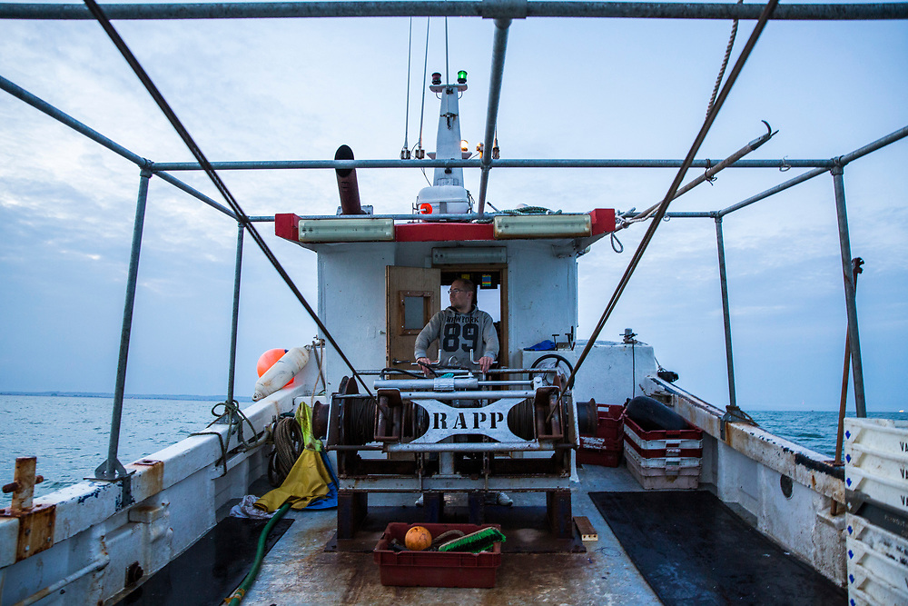 Lowering the trawler nets into the sea for the first trawl of the evening. Luke, a Folkestone based fisherman out trawling for a solo12 hour night shift on a fishing trip in his boat Valentine (FE20), Hythe Bay, the English Channel, United Kingdom. <br /> (photo by Andrew Aitchison / In pictures via Getty Images)