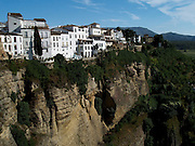 The cliffside city of Ronda, one of the most famous and spectacular towns in Spain. A hangout for Orson Wells and Ernest Hemingway, Ronda is well known for its gorge-straddling bridge and its bullring. Ronda, Andalusia, Spain.