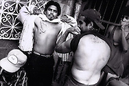 Gang members show tattoos at the La Mesa Penitentiary in Tijuana, Mexico.  1994