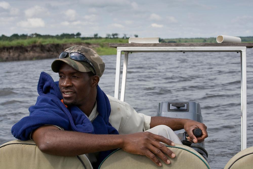 Africa, Botswana, Chobe National Park, Safari guide pilots motor boat during wildlife cruise along Chobe River