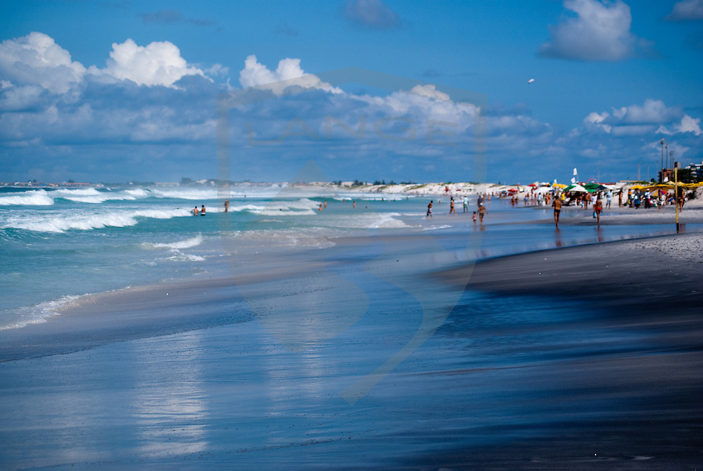 atlantic beach ocean landscape with cloud filled blue sky  and beach goers at cabo frio beach in rio de janeiro brazil.