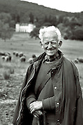 close up of shepherd with flock in background,black and white verticle