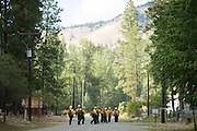 Wildland firefighters walk down North Main Street in Conconully Friday August 21, 2015 to take their positions and hold a fire line. <br />