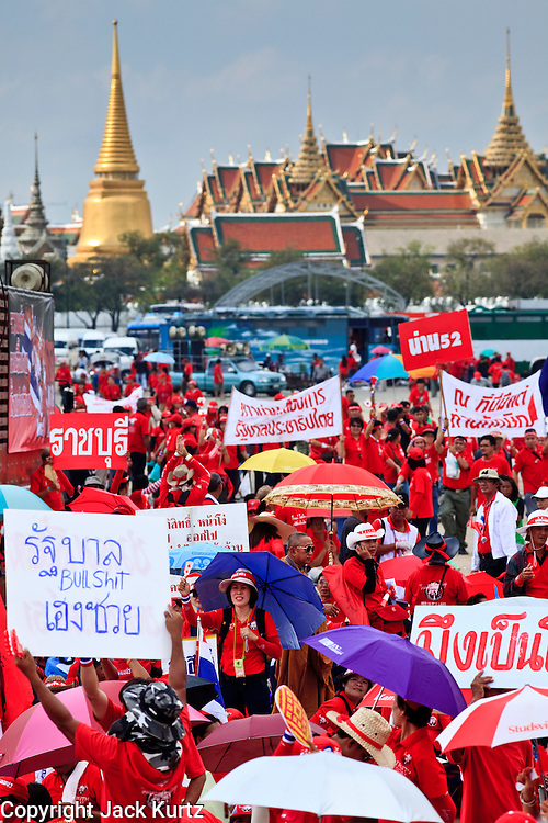 "26 MARCH 2009 -- BANGKOK, THAILAND: Anti-government protestors gather in front of the ""Grand Palace,"" historically the seat of the Thai Monarchy. More than 30,000 members of the United Front of Democracy Against Dictatorship (UDD), also known as the ""Red Shirts""  and their supporters gathered on Sanam Luang (the vast open field in front of the Palace) and descended on central Bangkok March 26 to start a series of protests against and demand the resignation of current Thai Prime Minister Abhisit Vejjajiva and his government. The protest is a continuation of protests the Red Shirts have been holding across Thailand. Thaksin was deposed in a coup and went into exile rather than go to prison after being convicted on corruption charges. He is still enormously popular in rural Thailand.  PHOTO BY JACK KURTZ"