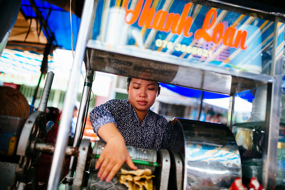 A woman selling sugarcane juice at the local market in Chau Doc, Vietnam.