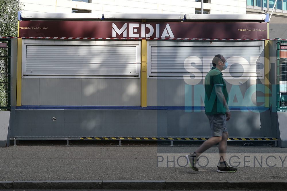 A man wearing a mask walks past the closed media ticket office before the Serie A match at Stadio Grande Torino, Turin. Picture date: 20th June 2020. Picture credit should read: Jonathan Moscrop/Sportimage