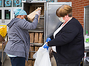 22 APRIL 2020 - DES MOINES, IOWA: FADYA HAROUN (left) and SUSAN AYALA pack up grab and go meals for students at Edmunds Elementary School. Schools in Iowa are closed for the rest of the school year because of the COVID-19 (Coronavirus/SAR-CoV-2) pandemic. Des Moines Public Schools expanded their school lunch and distance learning efforts this week. Lunches are being distributed at all of the district's elementary and middle schools and officials have started distributing computers so students can participate in distance learning. The meal distribution was done according to social distancing guidelines.           PHOTO BY JACK KURTZ