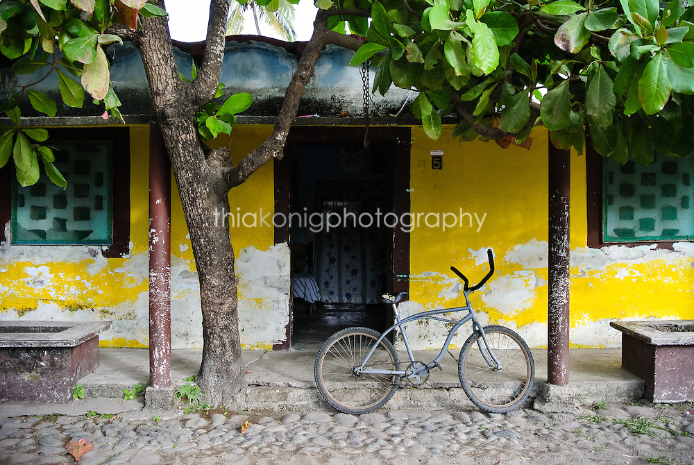 Quiet cobblestone street scene with yellow walls and bicycle, San Blass, Mexico