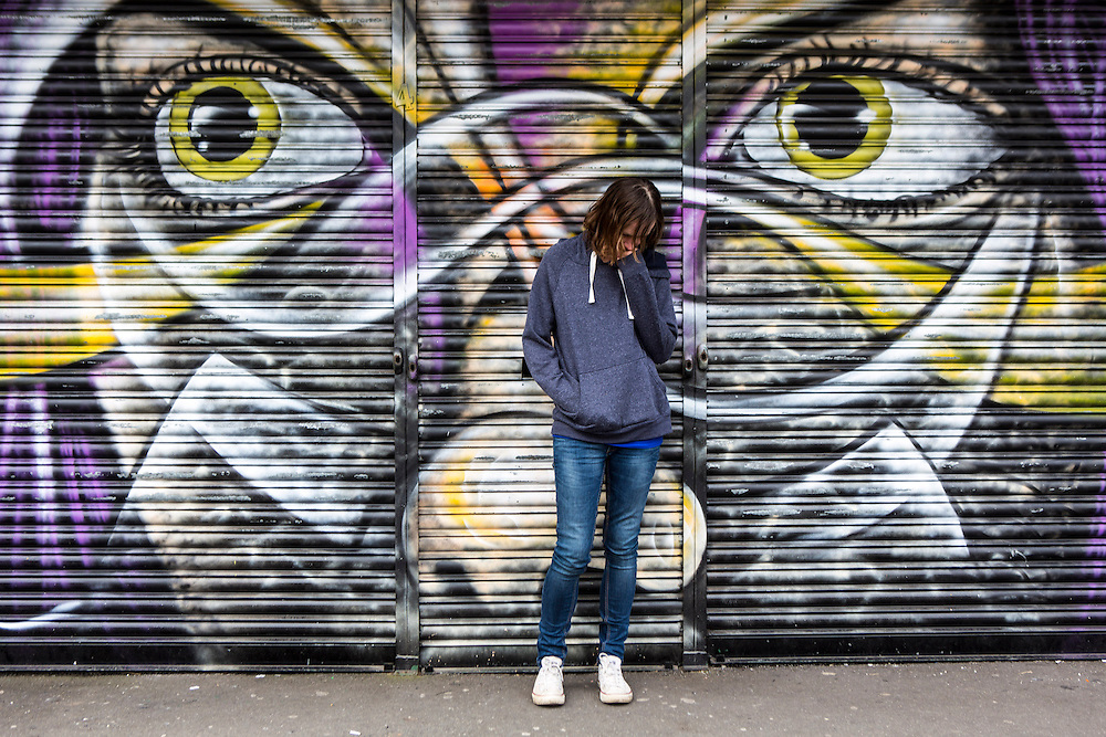 A vulnerable teenage youth hanging about in front of a graffiti painted shop front on a Hackney estate, London. UK