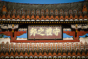 "Photo shows the roof and placard of Shureimon Gate inside the grounds of Shuri-jo Castle park in Naha, Okinawa Prefecture, Japan, on June 25, 2012. Shureimon was built during the reign of King Sho Sei, 1527-1555 and the placard reads ""A Land of Prosperity.""  Photographer: Robert Gilhooly"