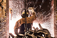 Pacific Steel Casting Company employee saws a part