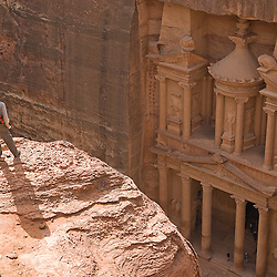 Man standing near the edge to take a better view of the Treasury from the top, Petra, jordan, Asia.
