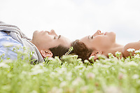 Side view of young couple sleeping on grass against clear sky
