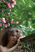 Artistic tranquil portrait of a young beautiful woman standing outdoors by the garden fence under a blooming camellia tree pink flowers with a serene, dreamy expression.