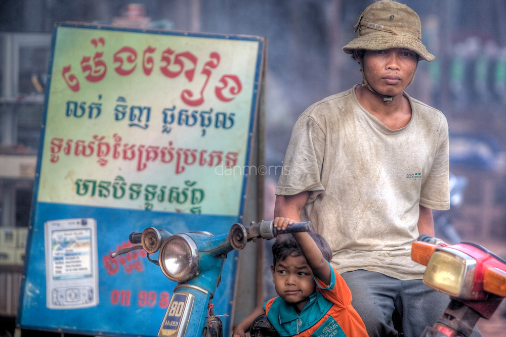 Young boy dreams of driving scooter in Snuol, Cambodia