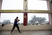 Un élève s'entraîne dans le gymnase de Bhiwani Boxing Club, juste au dessous de deux des avertissements que le coach a accroché un peu partout dans le gymnase