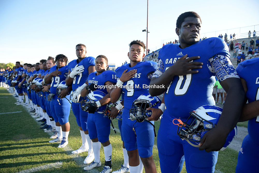 Apopka offensive linemen Will Barnes (67) and Ed Montilus (70) stand with teammates for the playing of the national anthem before a spring high school football game against Orange City University in Apopka, Fla., Thursday, May 25, 2017. (Photo by Phelan M. Ebenhack)