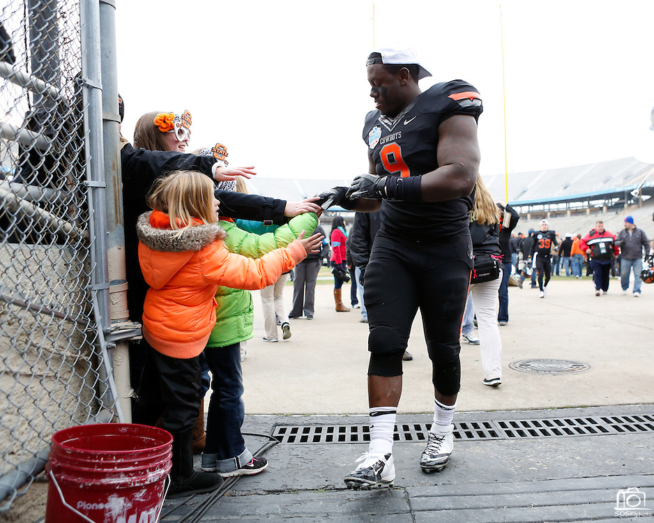Oklahoma State's Kye Staley (9) gives his gloves to fans after beating Purdue, 58-14, in the inaugural Heart of Dallas Bowl at Cotton Bowl Stadium at Fair Park in Dallas, Texas, on January 1, 2013.  (Stan Olszewski/The Dallas Morning News)