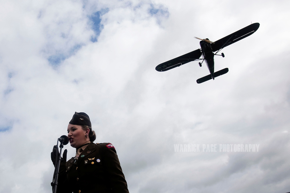 WWII-era performer, Kelly Ann Sproul, sings as a vintage plane flies overhead during the unveiling of a monument on the 68th anniversary of D-Day, on June 6, 2012, in Saint Marie du Mont, France . While the number of male re-enactors grossly outnumber the female, several women take on the role of WWII civilians, nurses and entertainers. Thousands of people throughout England and Europe belong to WWII re-enactment groups, flocking to numerous war-themed shows and events every year, where WWII is frequently the dominant theme. Dozens of WWII re-enactment groups, strive to portray military personnel and civilians of the era, spending thousands of dollars of their own money adorning themselves with authentic uniforms, vehicles and paraphernalia. (Photo by Warrick Page)