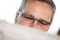 Österreich, Geschäftsmann macht Pause in Restaurant, Zeitung lesend, Portrait, Nahaufnahme