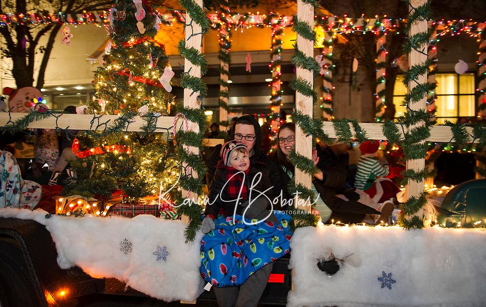 Holiday Parade floats head down Main Street towards Stewart Park on Sunday evening.  (Karen Bobotas/for the Laconia Daily Sun)