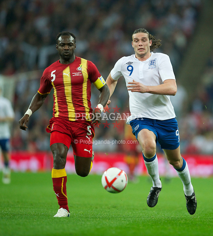 LONDON, ENGLAND - Tuesday, March 29, 2011: England's Andy Carroll in action against Ghana's captain John Mensah during the international friendly match at Wembley Stadium. (Photo by David Rawcliffe/Propaganda)