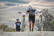 Jeffrey Summers pushes his and Elmarie Steyn's mountain bikes up the infamous Merino Monster climb during Stage 2 of the Momentum Health Tankwa Trek, presented by Biogen, on Saturday the 11th of February 2017.
