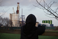 © Licensed to London News Pictures . 26/01/2014 . Salford , UK . A protester looks across a field towards the fracking site . Protesters march to an iGas fracking exploration site at Barton Moss , Salford , today (Sunday 26th January 2014) . A long term protest camp has been established on an access road leading to the site and today (26th January) protesters from other areas of the country travelled to the site to join with other protesters against fracking . Photo credit : Joel Goodman/LNP