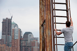 Man climbing up an industrial ladder with a view of Lower Manhattan