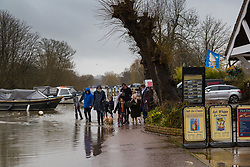 People walking in Henley on Thames, Oxfordshire, encounter floodwaters on the road as heavy rains in the River Thames catchment area and saturated ground causes the river to rise to within inches of bursting its banks.. April 02 2018.