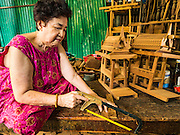 02 NOVEMBER 2016 - BANGKOK, THAILAND: HONG, 77 years old, the matriarch of the last family making spirit houses in the Ban Fuen community, saws teak wood for use in a spirit house. There used to be 10 families making traditional spirit houses out of teak wood in Ban Fuen, a community near Wat Suttharam in the Khlong San district of Bangkok. The area has been gentrified and many of the spirit house makers have moved out, their traditional wooden Thai houses replaced by modern apartments. Now there is just one family making the elaborate spirit houses. The spirit houses are made by hand. It takes three days to make a small one and up to three weeks to make a large one. Prices start at about $90 (US) for a small one. The largest, most elaborate ones can cost over $1,000 (US). Almost every home and most commercial buildings in Thailand have a spirit house, which is a shrine to the protective spirit of a the land. Spirit houses are also common in Burma, Cambodia, and Laos.        PHOTO BY JACK KURTZ